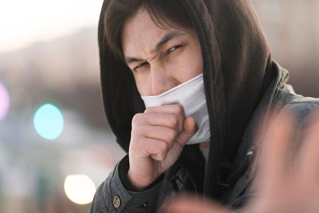 Vista laterale della tosse malata dell'uomo