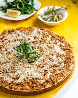 Vista laterale della tradizionale cucina turca lahmacun con carne macinata di formaggio e limone