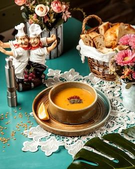 Vista laterale della zuppa di lenticchie merci in una ciotola con una fetta di limone