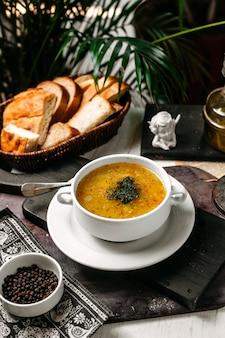 Vista laterale della zuppa di piselli e lenticchie con zafferano ed erbe in una ciotola bianca