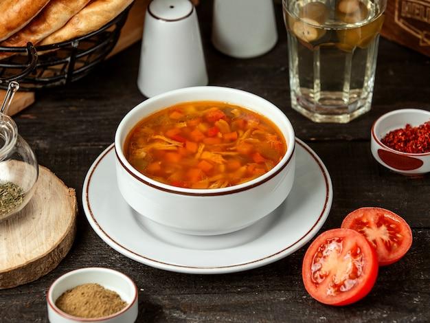 Vista laterale della zuppa di pollo con carota e pomodori in una ciotola bianca