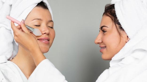 Vista laterale delle amiche che applicano prodotti per la cura della pelle