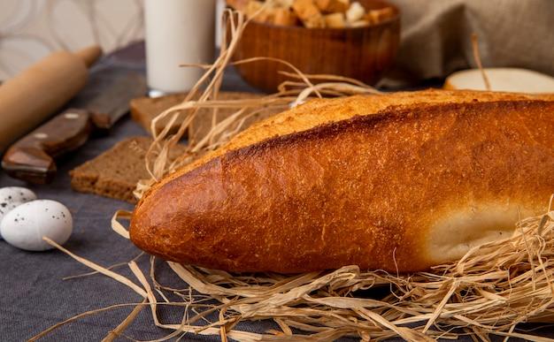 Vista laterale delle baguette su paglia con l'uovo su fondo marrone rossiccio