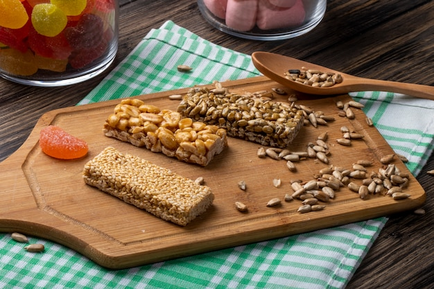 Vista laterale delle barre di miele con i semi di sesamo e di girasole delle arachidi su un bordo di legno su rustico