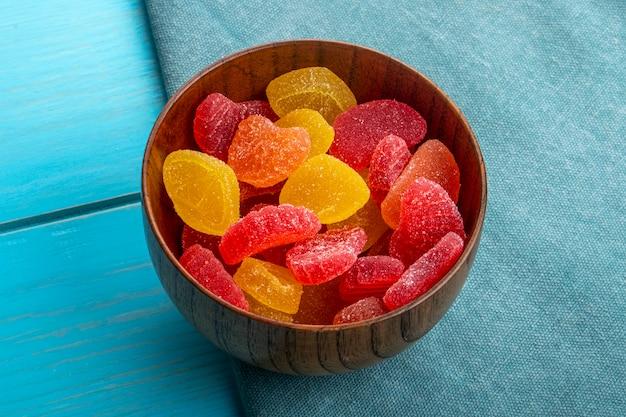 Vista laterale delle caramelle della marmellata d'arance in una ciotola di legno sull'azzurro