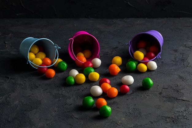 Vista laterale delle caramelle di cioccolato multicolori sparse dai piccoli secchi sul nero