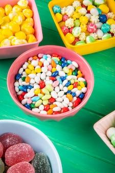 Vista laterale delle caramelle di zucchero dolci variopinte in ciotole su fondo di legno verde