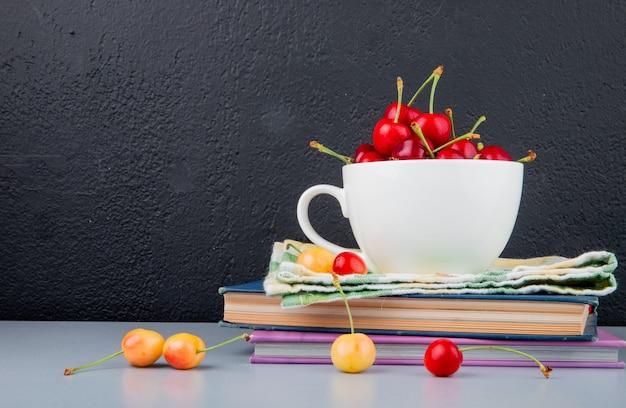 Vista laterale delle ciliege rosse in tazza sul panno e sui libri con le ciliege gialle su superficie blu e su fondo nero
