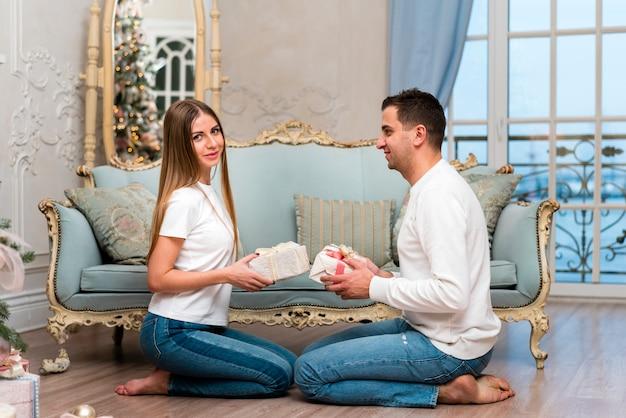 Vista laterale delle coppie che posano con i presente davanti al sofà