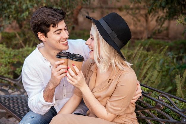 Vista laterale delle coppie di smiley al parco con le tazze di caffè