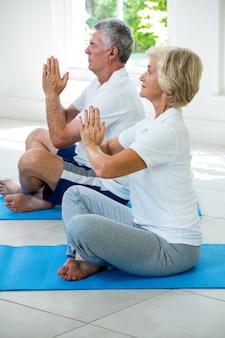 Vista laterale delle coppie senior attive che eseguono yoga