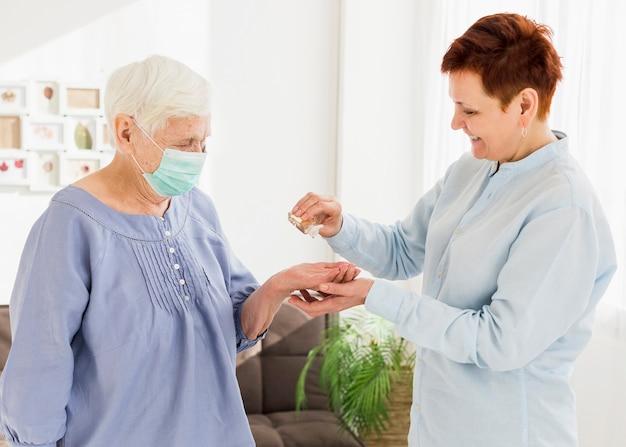 Vista laterale delle donne anziane che disinfettano le loro mani