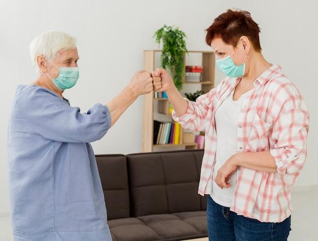 Vista laterale delle donne anziane con maschere mediche che sbattono i pugni per salutarsi