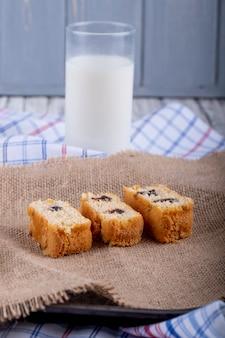 Vista laterale delle fette del pan di spagna con cioccolato su tela di sacco con un bicchiere di latte