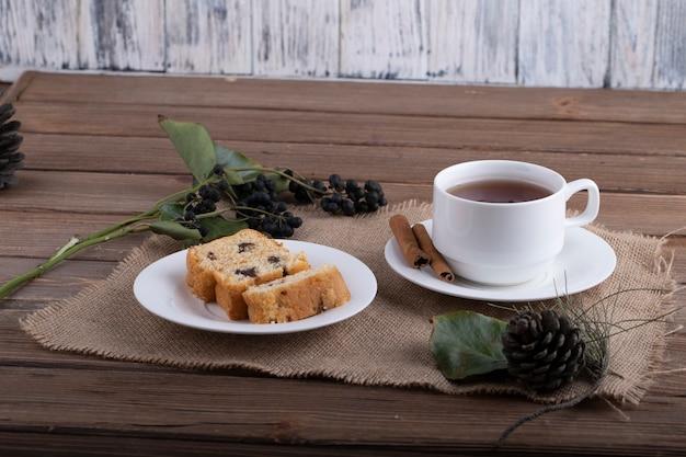 Vista laterale delle fette del pan di spagna su un piatto con una tazza di tè nero su rustico