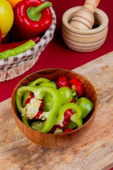 Vista laterale delle fette del pepe in ciotola sul tagliere con le verdure come merce nel carrello del pomodoro del pepe con il frantoio dell'aglio sul bordo