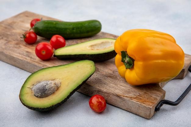 Vista laterale delle fette fresche dell'avocado su un bordo di legno del kitchrn con il cetriolo dei pomodori ciliegia e il peperone dolce giallo su superficie bianca