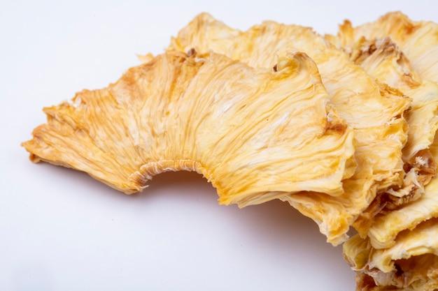 Vista laterale delle fette secche dell'ananas isolate su fondo bianco