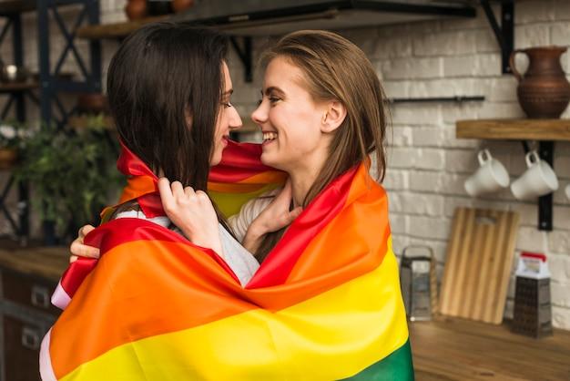 Vista laterale delle giovani coppie romantiche della lesbica avvolte nella bandiera del lbgt