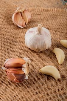 Vista laterale delle lampadine dell'aglio e degli spicchi d'aglio sbucciati sul fondo della tela di sacco