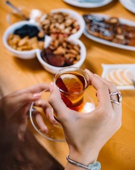 Vista laterale delle mani che tengono il vetro di armudu con tè nero