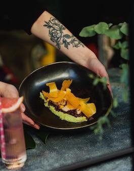 Vista laterale delle mani che tengono una banda nera con l'humus verde degli spinaci con riso sbramato e gamberetti