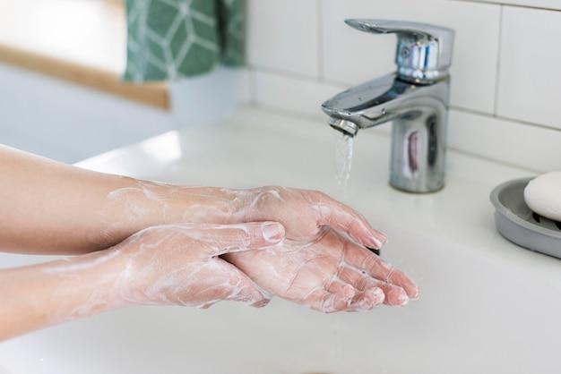 Vista laterale delle mani di lavaggio della persona con sapone nel bagno