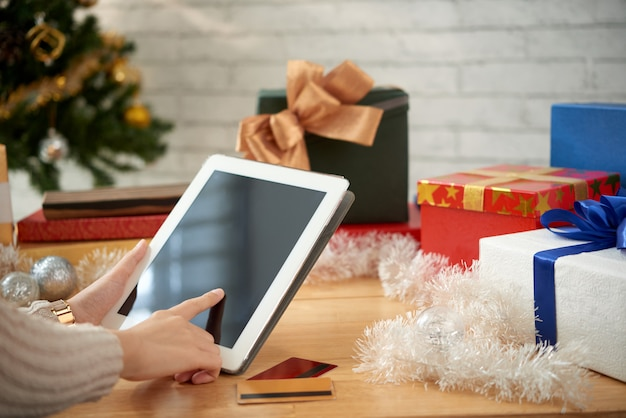 Vista laterale delle mani femminili che comprano i regali per il natale online