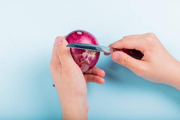 Vista laterale delle mani maschii che sbucciano cipolla rossa con il coltello su fondo blu