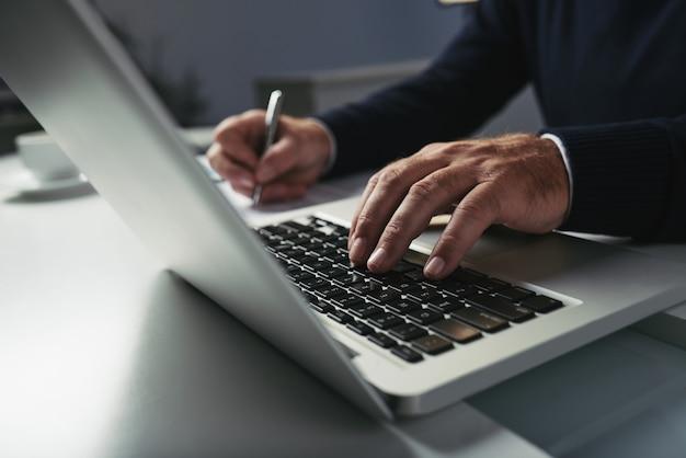 Vista laterale delle mani maschii che scrivono sulla tastiera del computer portatile