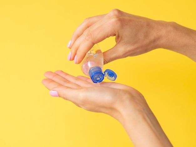 Vista laterale delle mani usando disinfettante per le mani