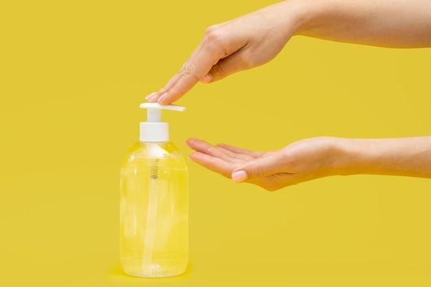 Vista laterale delle mani usando sapone liquido