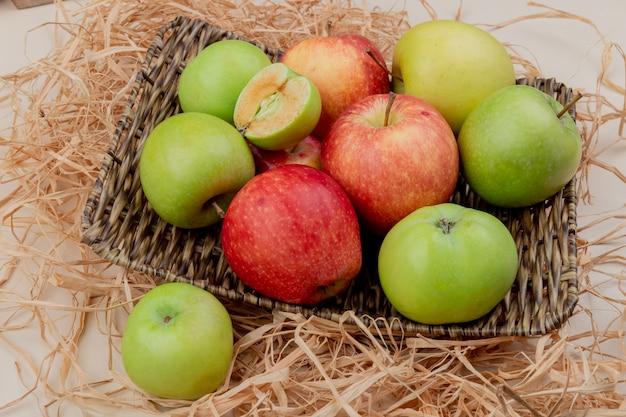 Vista laterale delle mele nel cestino piatto su paglia su avorio