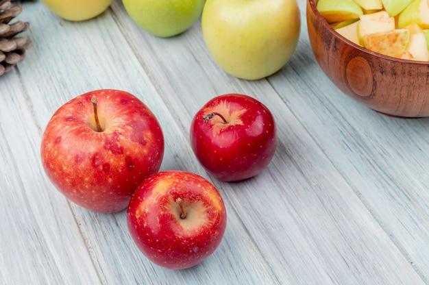 Vista laterale delle mele rosse con quelle gialle e verdi e ciotola di fette della mela su fondo di legno