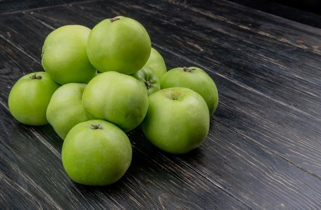 Vista laterale delle mele verdi su superficie di legno con lo spazio della copia