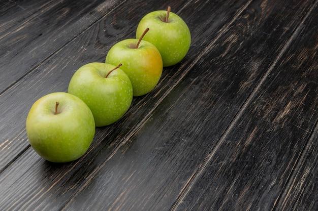 Vista laterale delle mele verdi su superficie di legno