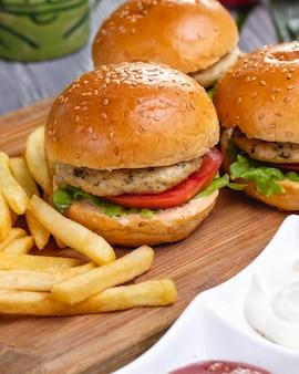 Vista laterale delle mini patate fritte della lattuga del pomodoro del pollo degli hamburger