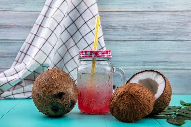 Vista laterale delle noci di cocco marroni con succo in un barattolo di vetro sulla tovaglia e sulla superficie di legno grigia