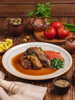Vista laterale delle olive di verdi di pomodoro della carne dei rotoli di cavolo