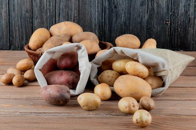 Vista laterale delle patate che si rovesciano dai sacchi su superficie e su fondo di legno con lo spazio della copia