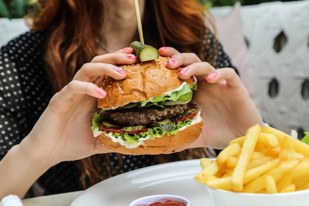 Vista laterale delle patate fritte della cipolla del cetriolo del pomodoro della lattuga dell'hamburger della carne della tenuta dell'uomo