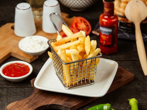 Vista laterale delle patate fritte nel cestino di filo metallico