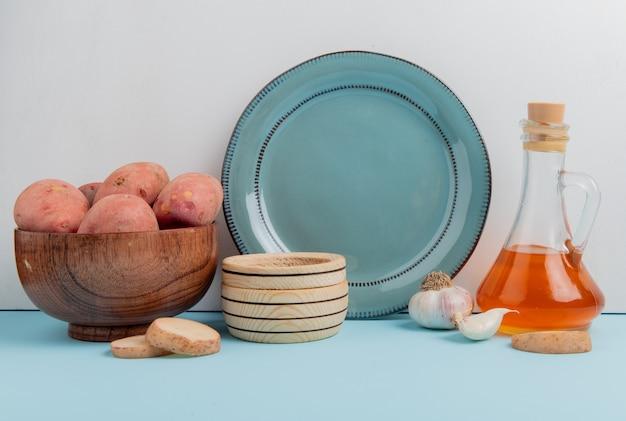Vista laterale delle patate in ciotola con burro fuso aglio e piatto vuoto su superficie blu e su fondo bianco