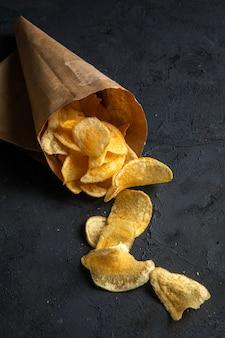 Vista laterale delle patatine fritte sparse da una borsa di pepe sul nero