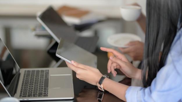 Vista laterale delle persone di affari che si consultano sul loro progetto con la compressa e il computer portatile digitali