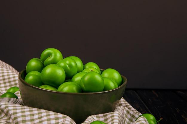 Vista laterale delle prugne acide verdi in una ciotola sul tessuto del plaid alla tabella scura
