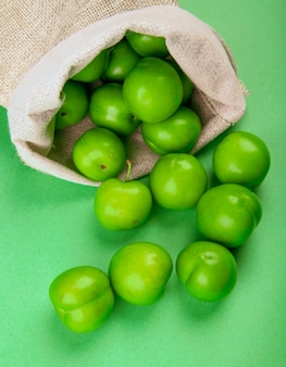 Vista laterale delle prugne acide verdi sparse da un sacco sulla tavola verde