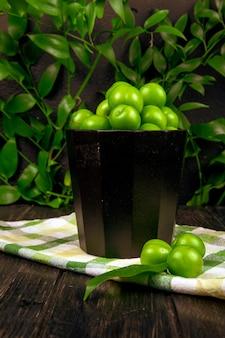 Vista laterale delle prugne verdi acide in una ciotola sul tovagliolo del plaid su superficie di legno alla tavola delle foglie verdi