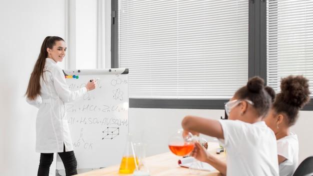Vista laterale delle ragazze che imparano a conoscere la chimica in classe