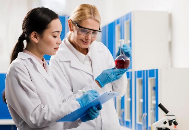 Vista laterale delle scienziate che analizzano sostanza in laboratorio